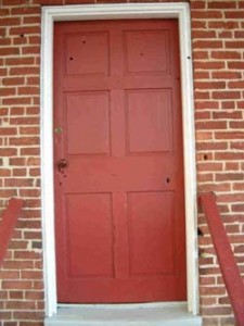 The red door with obvious bullet holes in