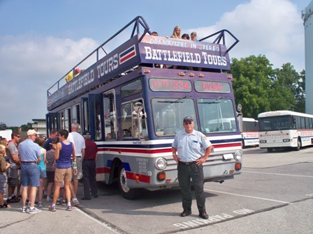 tour guide standing in front of double decker tour bus near Gettysburg Battlefield