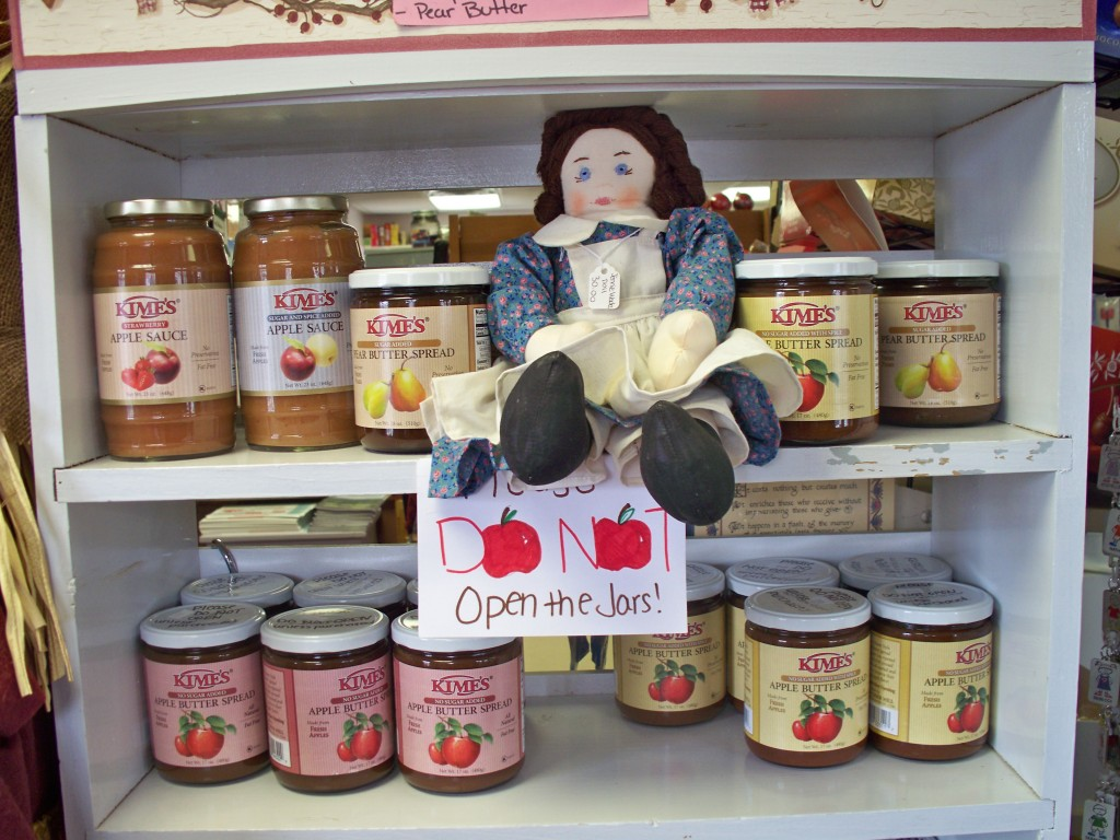 jennie wade doll sitting on a shelf with apple butter spread and sauce