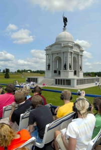 tour group on an open air double decker tour bus viewing a gettysburg monument