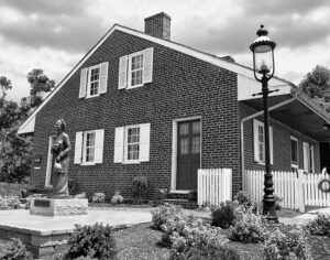 black and white photo of the side of the Jennie Wade House with her statue out front