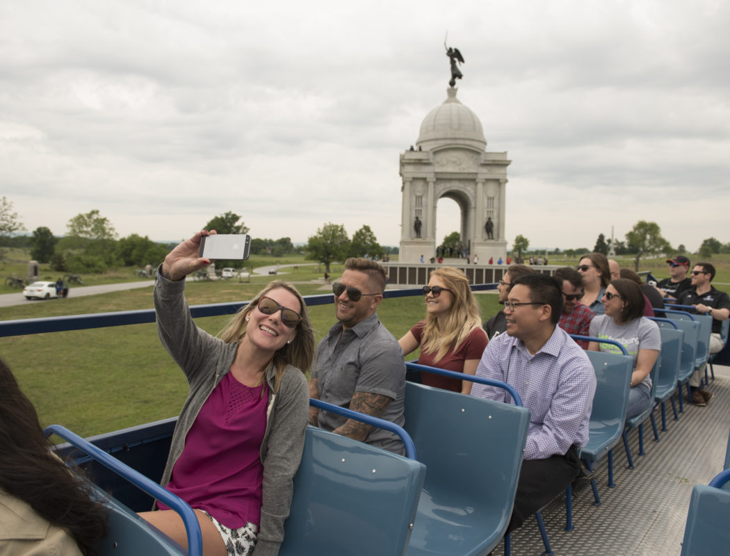 a woman taking a selfie on top of a gettysburg double decker bus