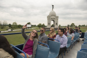 a woman taking a selfie on top of a gettysburg double decker bus