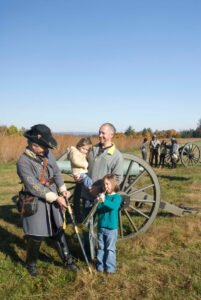 Gettysburg reenactor next to a cannon and family
