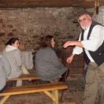 ghostly encounter tour guide talking to a group in the basement