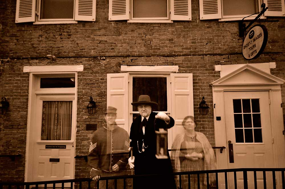 2 ghosts behind a guide out front of Gettysburg Ghost Tours office