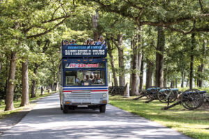 double decker gettysburg tour bus driving down a road lined by trees with cannons on the right side
